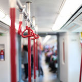Inside the subway car. Red handrails in the subway. Stock Photo