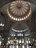 Inside Sultan Ahmed Mosque. A popular tourist site, the Sultan Ahmed Mosque continues to function as a mosque today; men still kneel in prayer on the mosque& x27 Stock Photography