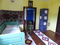 Inside of a traditional house in Romania. Travel destination. Yellow walls. Carpets on the floor and on the wall. Colored and decorated carpets. Green wood bed royalty free stock photo