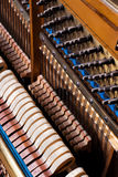 Close up of old inside element piano. Inside an Upright Piano. Felt Hammers used to strike Steel Strings and wound knobs to tune Stock Image