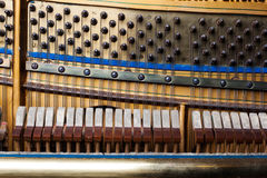 Close up of old inside element piano. Inside an Upright Piano. Felt Hammers used to strike Steel Strings and wound knobs to tune Royalty Free Stock Photography