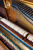 Close up of old inside element piano. Inside an Upright Piano. Felt Hammers used to strike Steel Strings and wound knobs to tune Royalty Free Stock Images