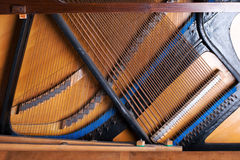 Close up of old inside element piano. Inside an Upright Piano. Felt Hammers used to strike Steel Strings and wound knobs to tune Stock Photos