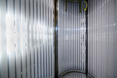 Inside the vertical tanning booth. Stock Photos
