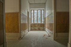 Inside view of abandoned sanatorium in Portugal. Old wood corridor in ruin with window at the end royalty free stock photo