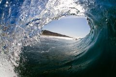 Inside view of a breaking wave on a tropical beach under a blue sky royalty free stock photos