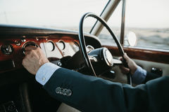 Inside view of classic luxury car being driven by man. Man driving an old classic and luxury car. Inside view stock images
