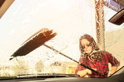 Inside view through the glass of pretty woman at carwash Stock Image