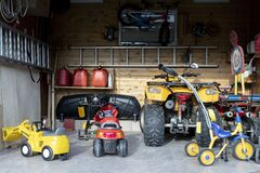 Free Inside View Open Door ATV Quad Bike Motorcycle Parking Messy Garage,clutter Stuff, Children Toys And Bicylce Storage Royalty Free Stock Images - 181045319
