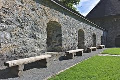 Inside view of the sunlit wall of Castle Hohenwerfen, Austria with shaded alcoves and rough wooden benches. Inside view of the sunlit wall of medieval Castle Royalty Free Stock Photography
