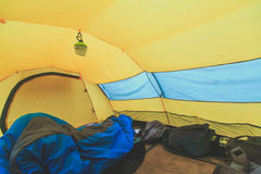 An inside view of tent, process of camping in fall or spring forest field, setting a tent covered Royalty Free Stock Photography