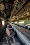 Railroad Dining Car - Abandoned Train. Inside a vintage but abandoned passenger dining car with red vinyl seats and a long, dusty and grimy counter Royalty Free Stock Photography