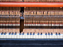 Inside of the vintage piano: string, pins, keys and hammers. Pattern of hammers and strings inside piano. One hummer in action while key is pressed. Old Stock Photos