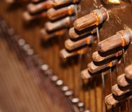 Inside a Vintage Upright Piano. Showing the rusting tuning knobs and coiled wires Stock Image