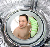 Inside washing machine. Displeased man working with washing machine holding a sock camera inside the machine Royalty Free Stock Photos