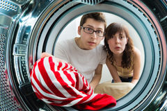 From inside the washing machine view. Funny couple loading clothes to washing machine. From inside the washing machine view Stock Photos