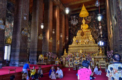 Inside the Wat Pho. Worshippers inside the Wat Pho in Bangkok, Thailand royalty free stock photo