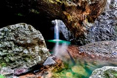 Inside waterfall of cave from natural bridge in Australia. Inside the waterfall falling down of a stone cave that brighten with colors from natural bridge in stock photo