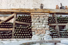 Inside a wine cellar with aged dust bottles and rustic wooden shelves. Historical storage of winery Royalty Free Stock Image