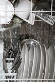 Inside working dishwasher. A view looking through a glass window at the inside of a modern home dishwasher as it works to wash the dishes royalty free stock photo