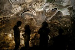 Zinzulusa Caves, near Castro on the Salento Peninsula in Puglia, Italy. Shadows of four people can be seen against the stone walls. Inside the Zinzulusa Caves royalty free stock images