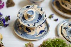 Insieme ceramico delle tazze e dei piatti Terraglie decorative sul bianco Fotografia Stock