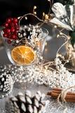 Insieme d'argento della cartolina di Natale sulla tavola nera, sul cono, sul vetro di vino vuoto, sul limone asciutto, sulla cann immagini stock