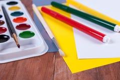 Insieme degli acquerelli, fogli di carta colorati e spazzole su una superficie di legno Fotografia Stock Libera da Diritti