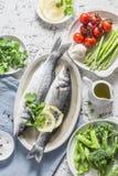Insieme degli ingredienti equilibrati sani per pranzo - branzino, asparago, pomodori, broccoli, piselli, olio d'oliva e spezie Su Fotografia Stock Libera da Diritti