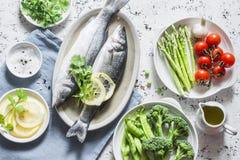 Insieme degli ingredienti equilibrati sani per pranzo - branzino, asparago, pomodori, broccoli, piselli, olio d'oliva e spezie Su Immagini Stock