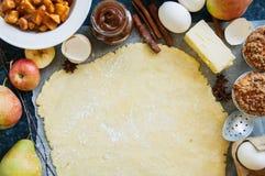 Insieme degli ingredienti per cuocere, pasta cruda per la torta, spezie, mela Fotografia Stock
