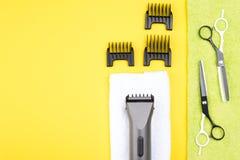 insieme degli oggetti differenti per il taglio dei capelli, bugie su un fondo giallo, c'è un posto per un'iscrizione Immagini Stock