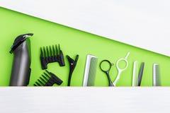 Insieme degli oggetti differenti per il taglio dei capelli, bugie su un fondo verde, c'è un posto per un'iscrizione Fotografia Stock