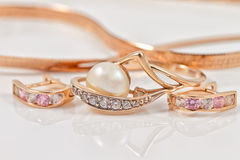 Insieme degli orecchini dell'oro e dell'anello di oro Fotografie Stock Libere da Diritti