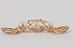 Insieme degli orecchini dell'oro e dell'anello di oro Fotografia Stock Libera da Diritti