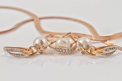 Insieme degli orecchini dell'oro e dell'anello di oro Immagini Stock