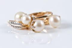 Insieme degli orecchini dell'oro e dell'anello di oro Fotografia Stock