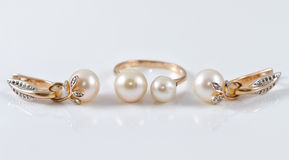 Insieme degli orecchini dell'oro e dell'anello di oro Fotografie Stock