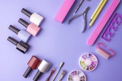 Insieme degli strumenti cosmetici per il manicure ed il pedicure su un fondo porpora Lucidi del gel, archivi di unghia e tagliato Immagini Stock
