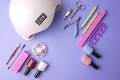 Insieme degli strumenti cosmetici per il manicure ed il pedicure su un fondo porpora Lucidi del gel, archivi di unghia e tagliato Fotografie Stock