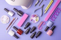 Insieme degli strumenti cosmetici per il manicure ed il pedicure su un fondo porpora Lucidi del gel, archivi di unghia e tagliato Immagine Stock Libera da Diritti