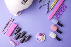 Insieme degli strumenti cosmetici per il manicure ed il pedicure su un fondo porpora Lucidi del gel, archivi di unghia e tagliato Immagine Stock