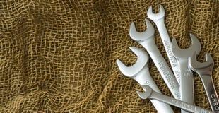 Insieme degli strumenti delle chiavi sulla disposizione del piano della lana di marrone scuro Immagine Stock Libera da Diritti