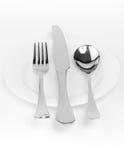 Insieme degli utensili dell'acciaio inossidabile sul piccolo piatto bianco Fotografia Stock