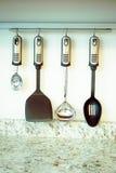 Insieme degli utensili della cucina che appendono sulla parete Fotografia Stock