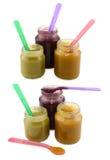 Insieme dei barattoli degli alimenti per bambini con i cucchiai Fotografia Stock