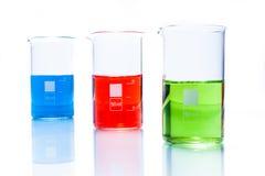 Insieme dei becher cilindrici resistenti di temperatura con il liquido di colore Fotografie Stock
