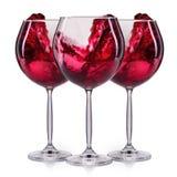 Insieme dei bicchieri di vino rossi con spruzzata e delle gocce su bianco Immagini Stock