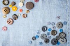 Insieme dei bottoni sulla vista superiore del tessuto blu Fotografia Stock