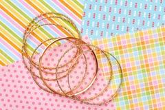 Insieme dei braccialetti dorati, fondo variopinto Fotografie Stock Libere da Diritti